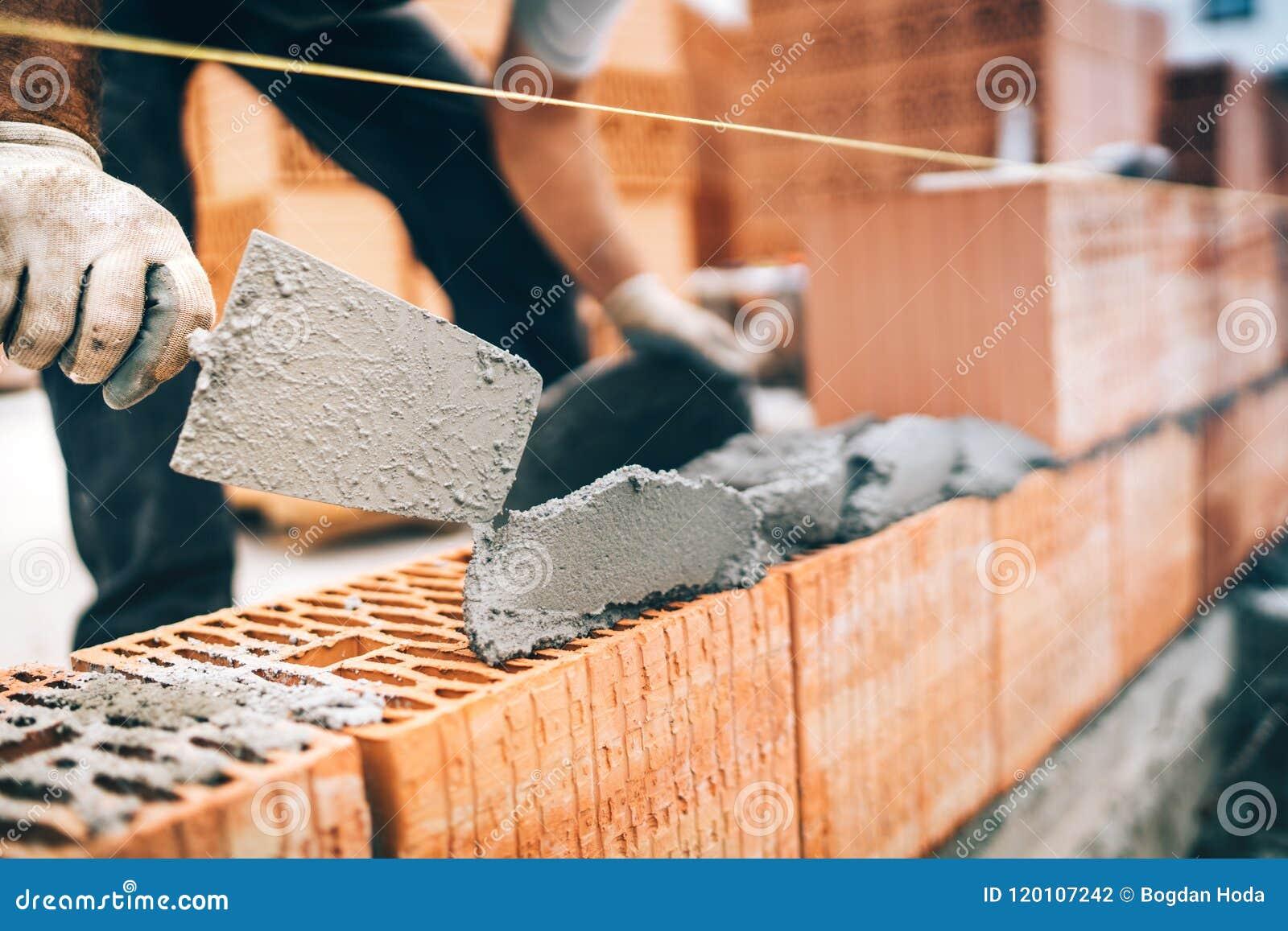 Detalles del trabajador de construcción, engranaje protector y paleta con las paredes de ladrillo del edificio del mortero