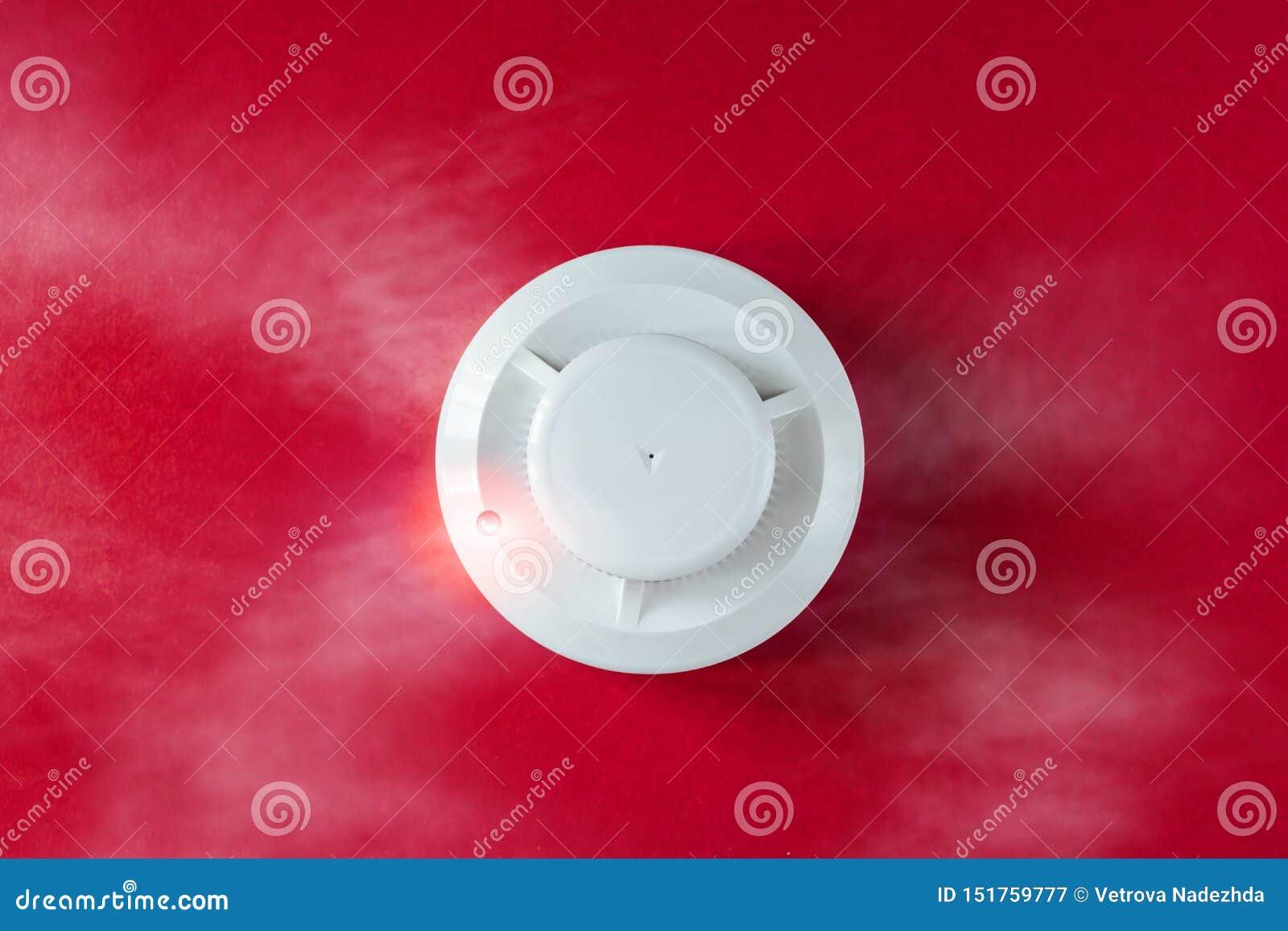 Detector del detector de humo y de incendios en un fondo rojo Endecha plana la alarma de incendio