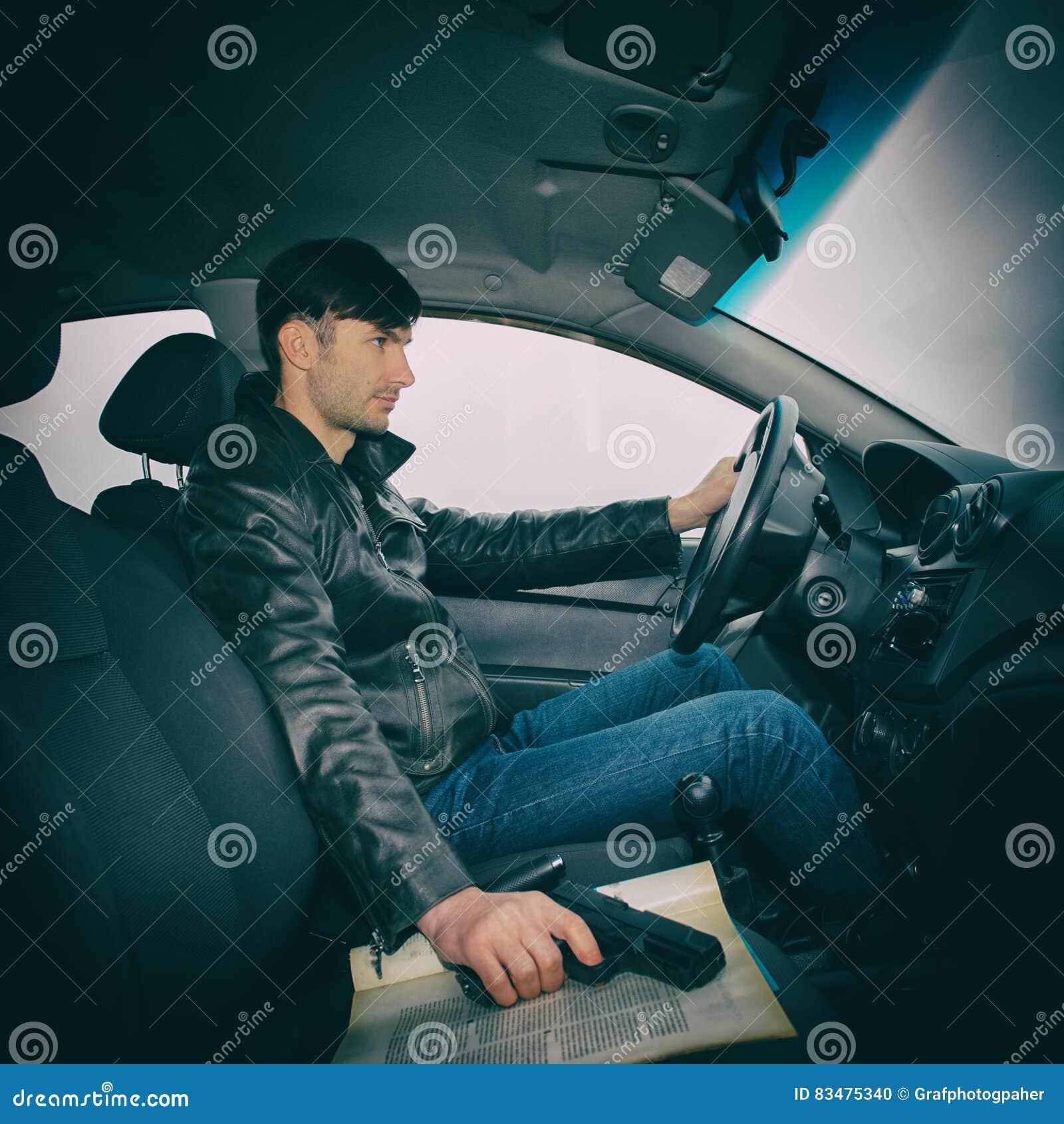 Detektiv mit einem Gewehr, das in einem Auto sitzt