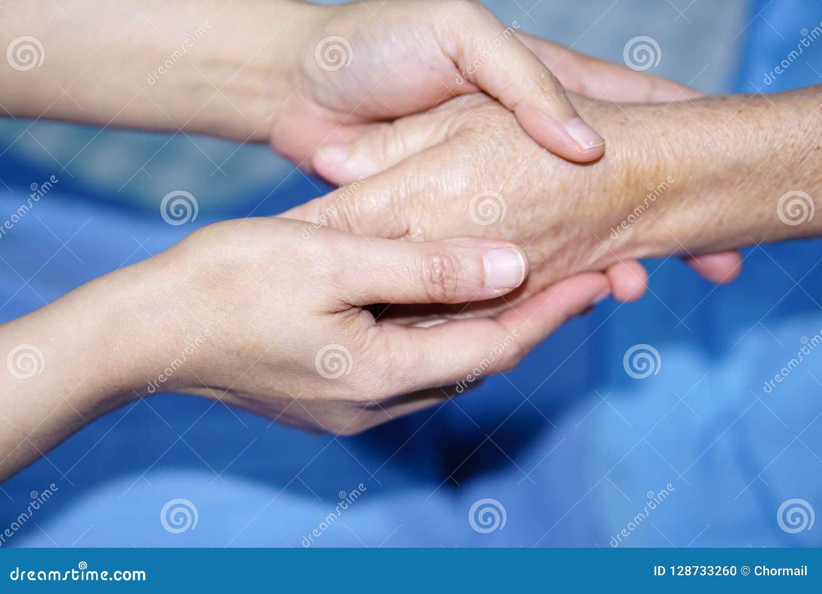 Detener al paciente mayor de las manos conmovedoras o mayor asiático de la mujer de la señora mayor con amor, cuidado, ayudando,