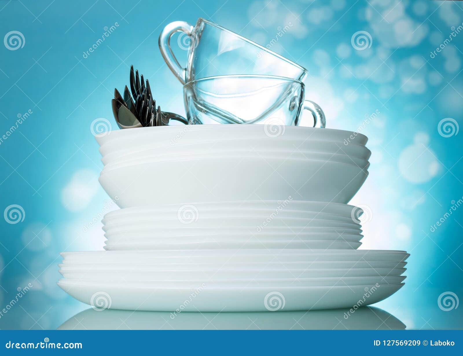 Determinado limpie los platos y las tazas lavados en fondo azul brillante hermoso