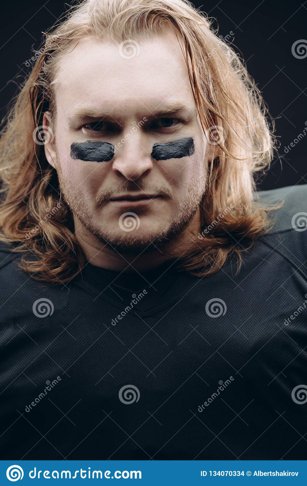 Determined American Football Player Posing With Painted Face And