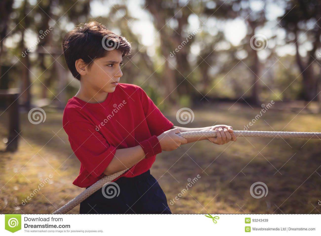 Determined boy practicing tug of war during obstacle course