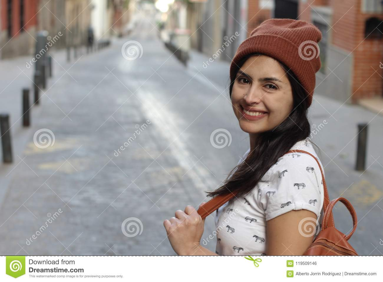 Determined ethnic woman smiling on the street