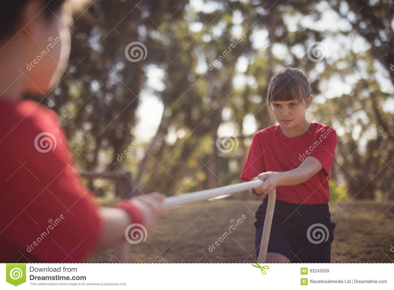 Determined kids practicing tug of war during obstacle course