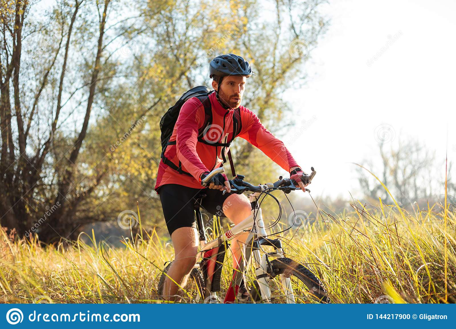Determined young bearded mountain biker riding along a path through tall grass