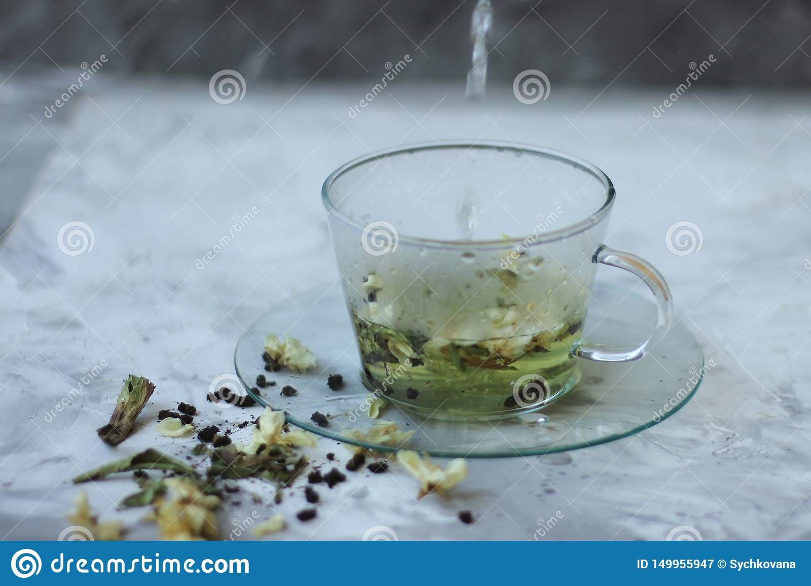 Detox food and drink healfhy lifestyle concept. Glass cup of green tea with jasmine on a gray background. Close
