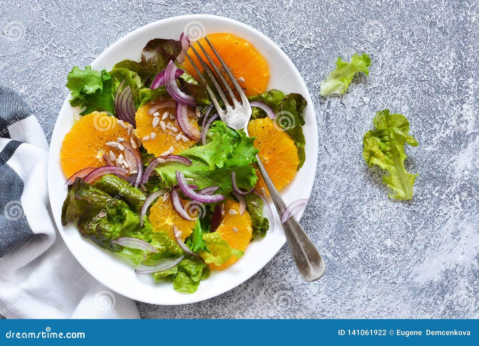 Detox odżywianie Sałatka z pomarańcze, cebulą i ziarnami na kuchennym stole,
