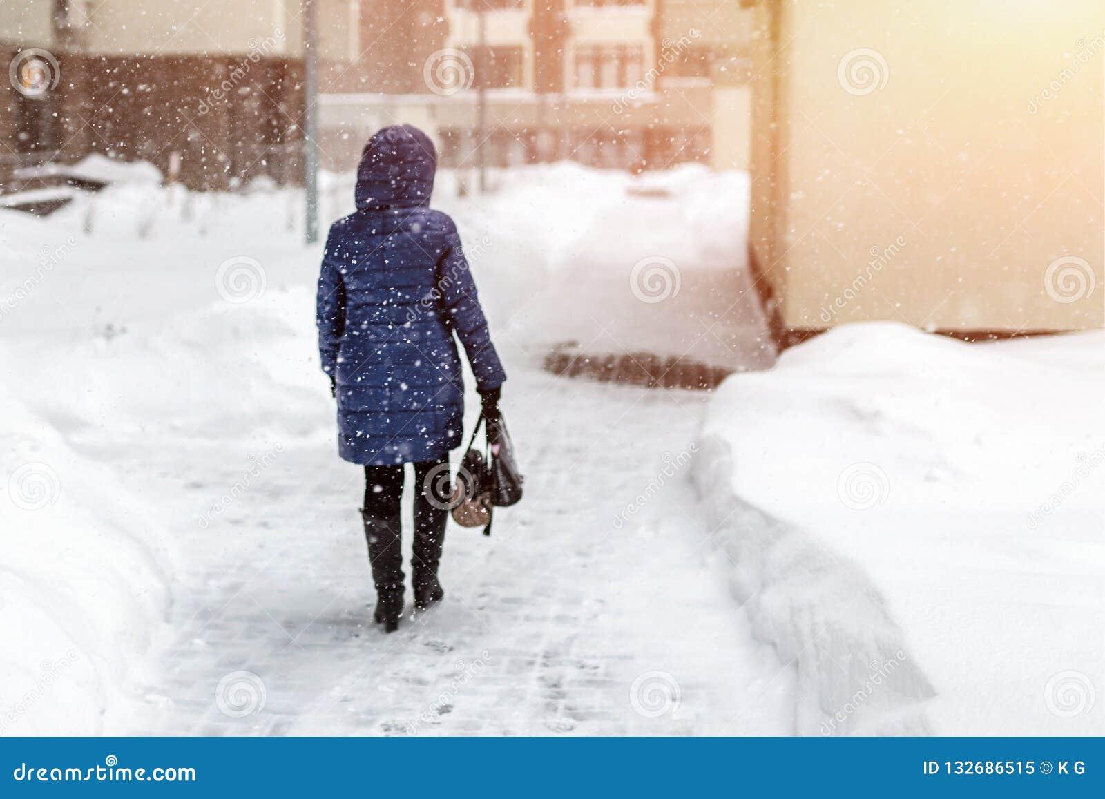 Detrás de la mujer en chaqueta del amanecer que camina a través de la calle de la ciudad durante las nevadas pesadas y ventisca e