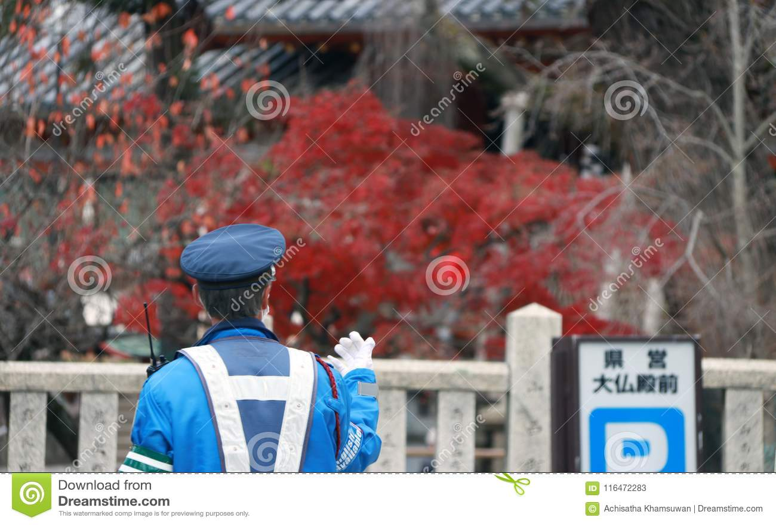 Detrás de la policía de tráfico japonesa en deberes de ejecución uniformes del azul en la calle