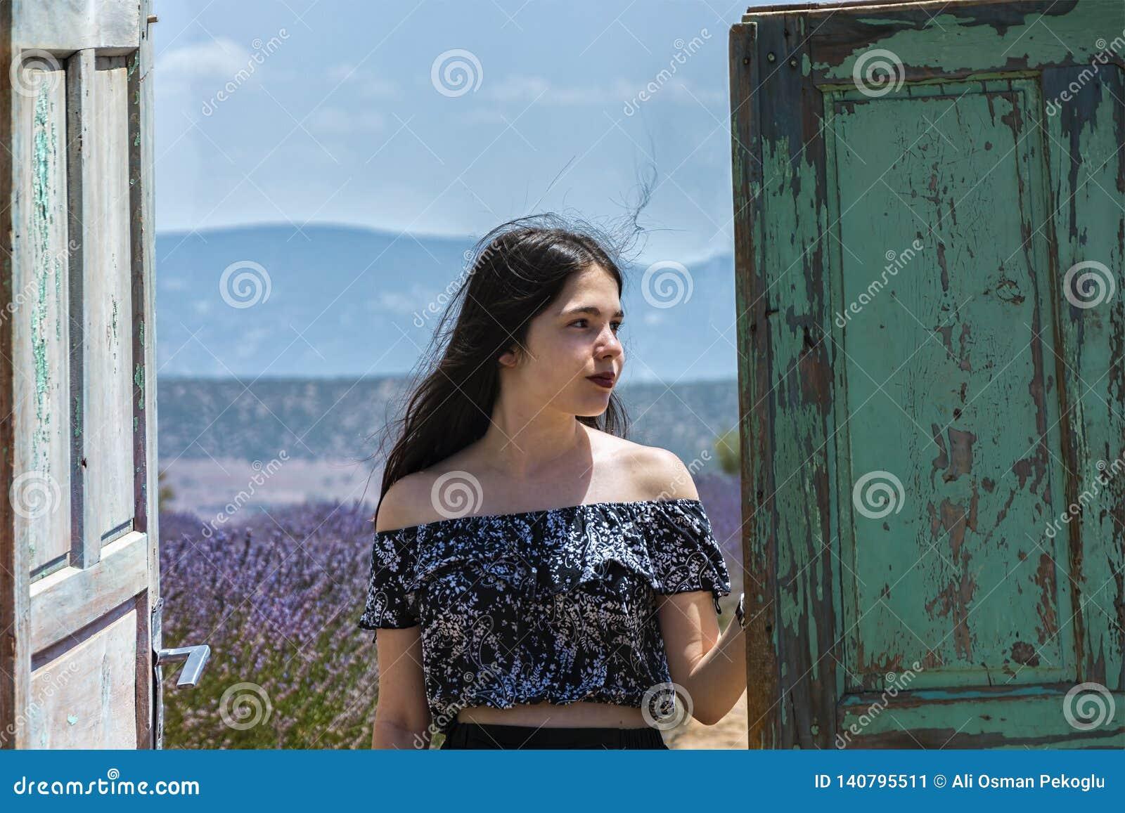 Detrás de la puerta de madera vieja, la chica joven