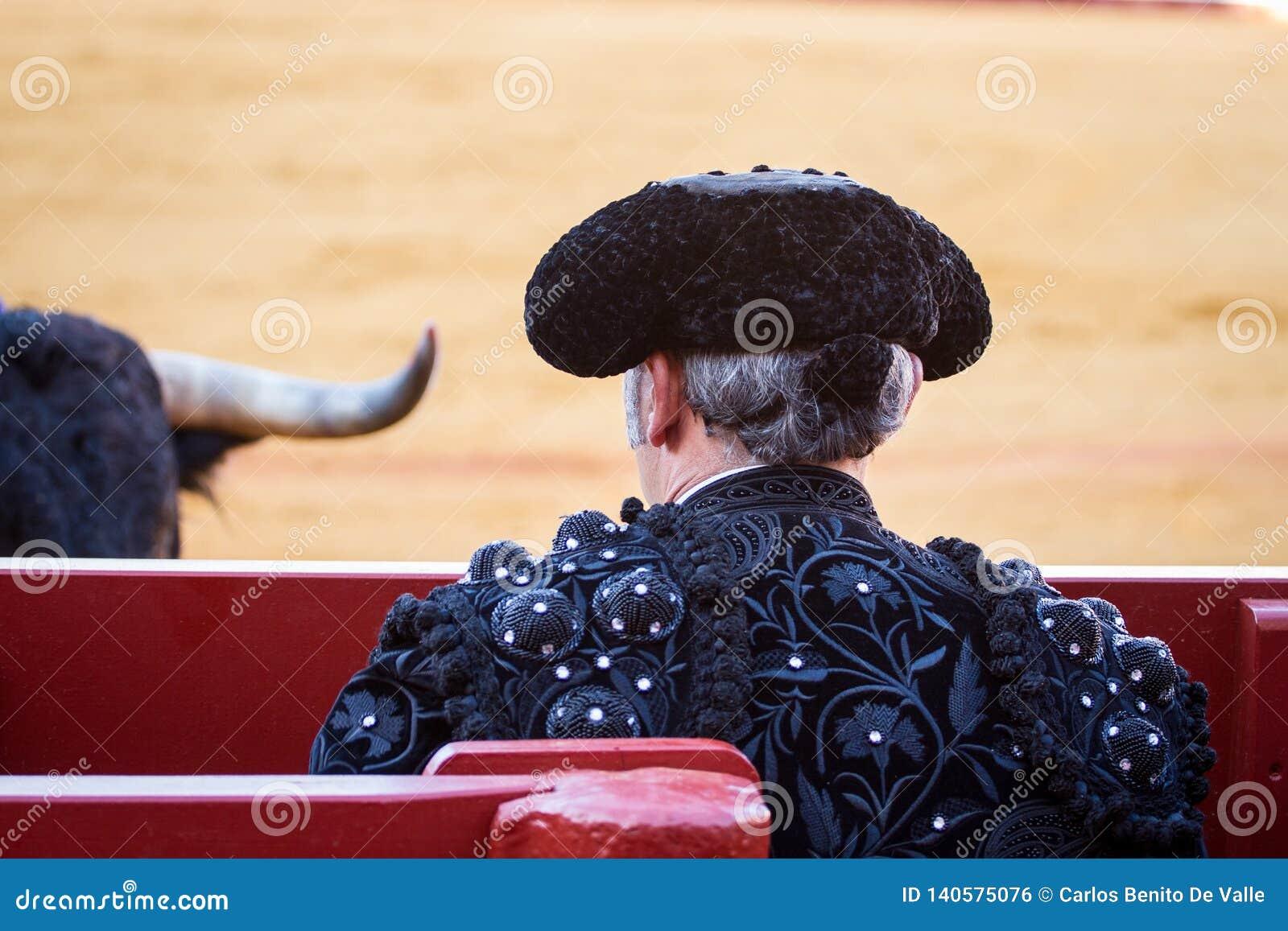 Detrás de un torero en la ropa negra que mira el toro