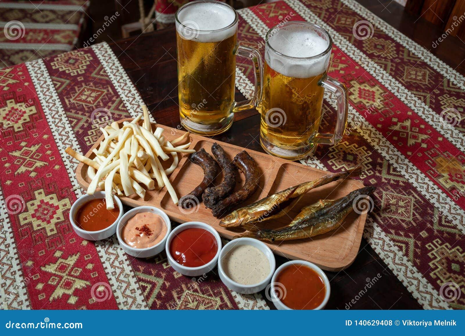 Detta är sparar av EPS10 formaterar Två öl och aptitretare på en träplatta med fem såser På en trätabell med en bordduk med natio