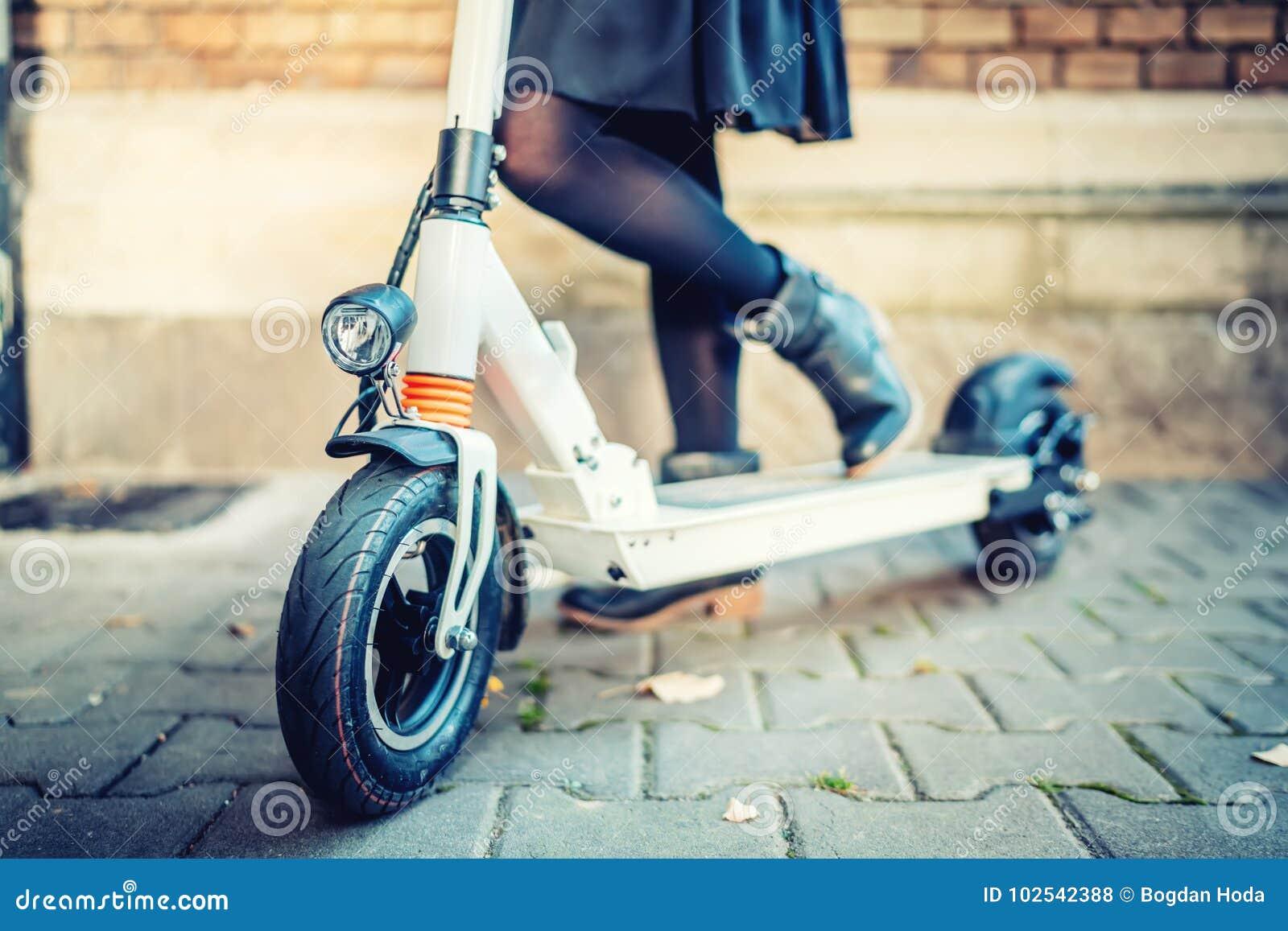 Dettagli di trasporto moderno, motorino elettrico di scossa, ritratto della ragazza che guida il trasporto della città