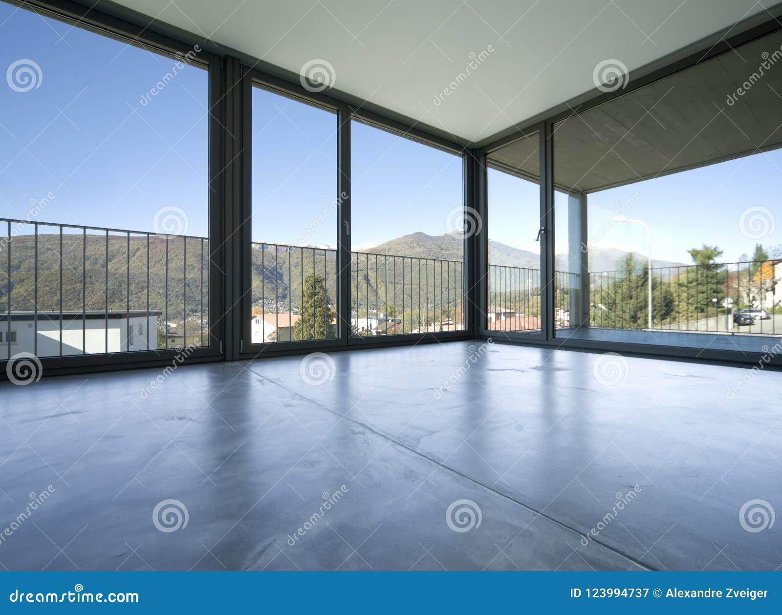 Dettaglio del salone vuoto con le grandi finestre che danno sulle montagne