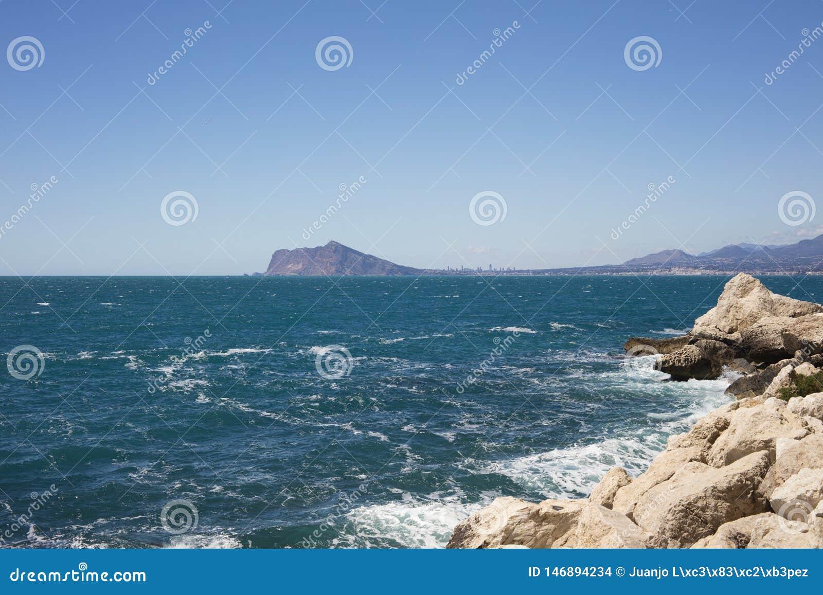 Dettaglio della spiaggia con turchese e del mare blu con Altea e Benidorm nel fondo