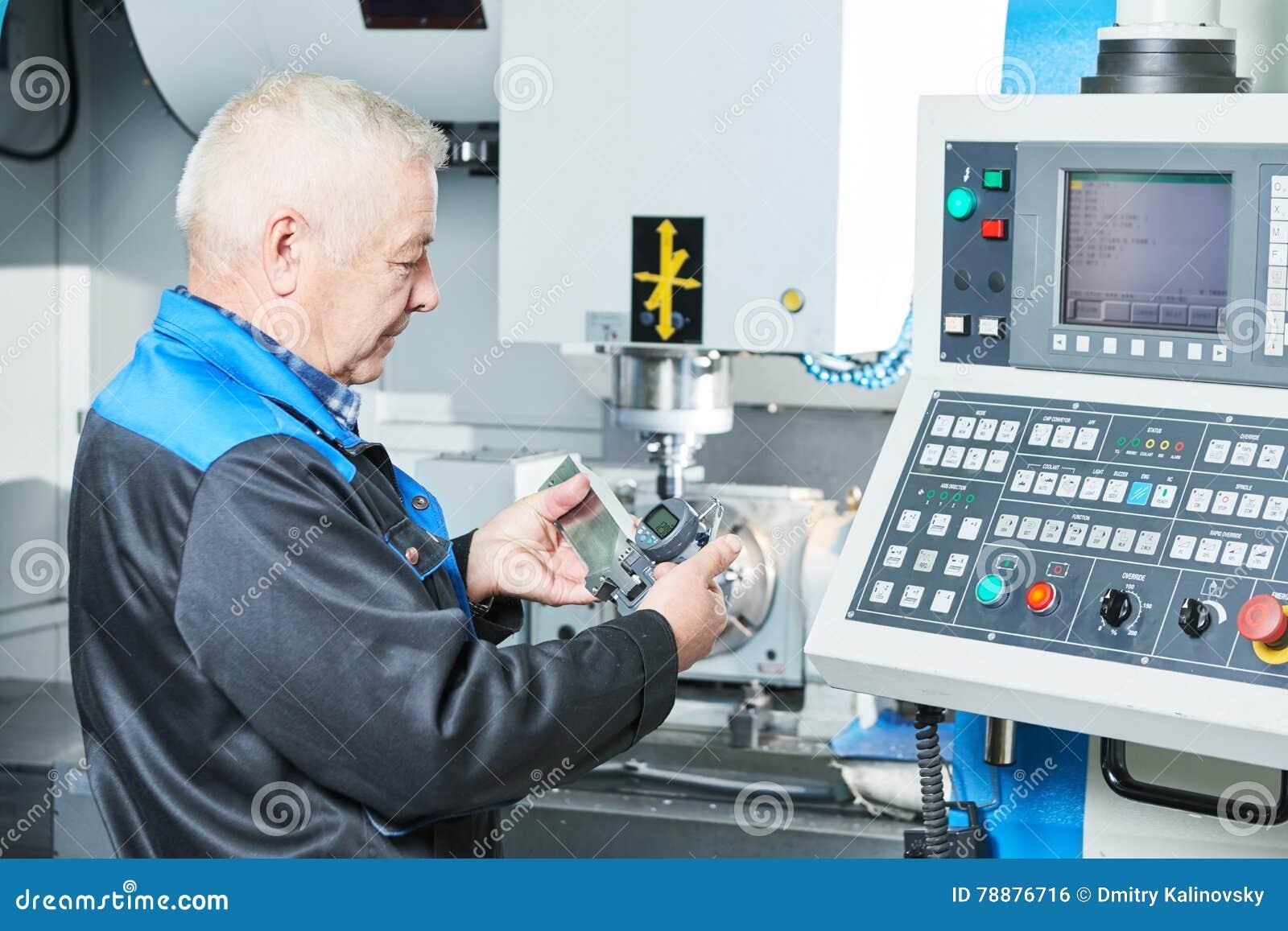 Dettaglio di misurazione del lavoratore dell industria vicino alla fresatrice di CNC