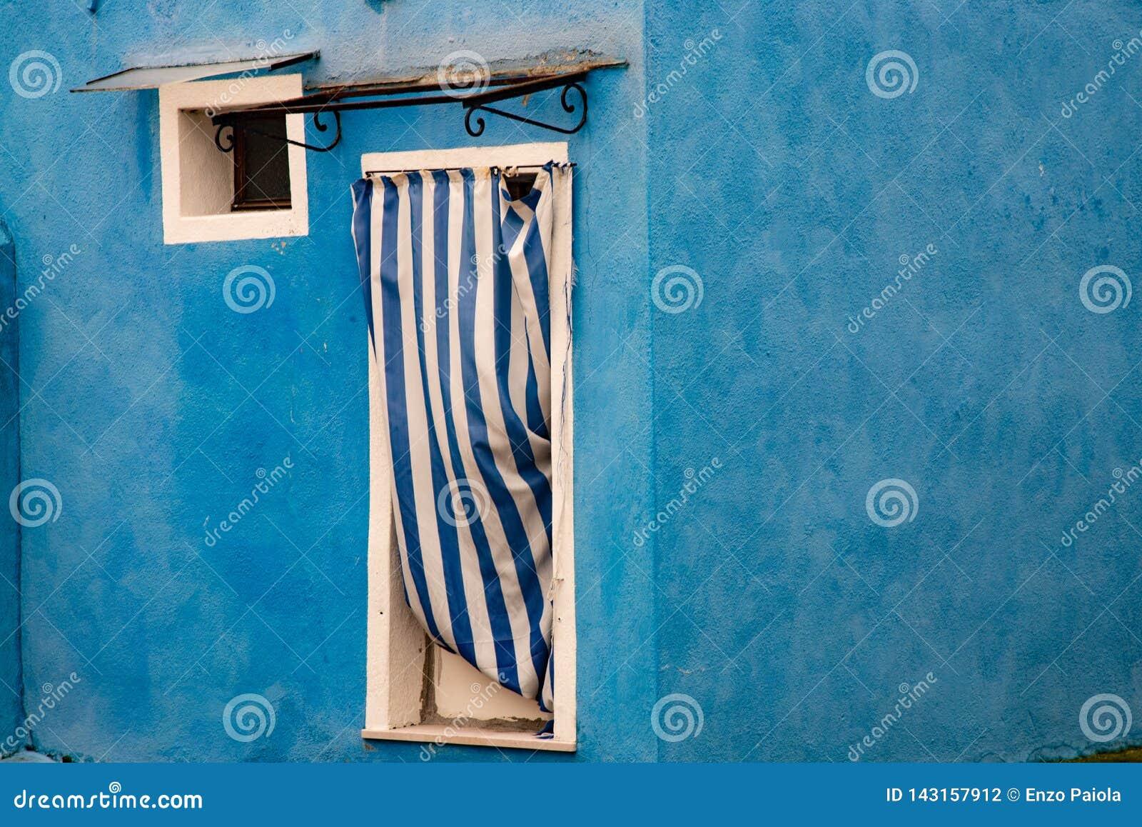 Deur met blauw en wit gestreept gordijn en klein vierkant venster