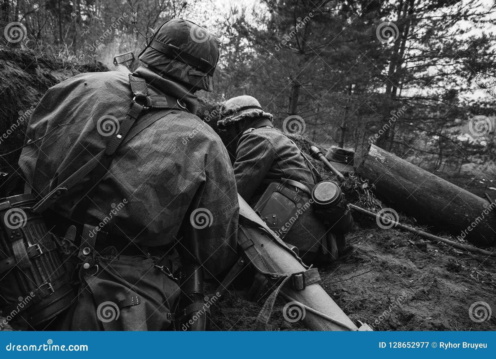 Deutsche Wehrmacht-Infanterie-Soldaten in Zweiter Weltkrieg verstecktem Sittin
