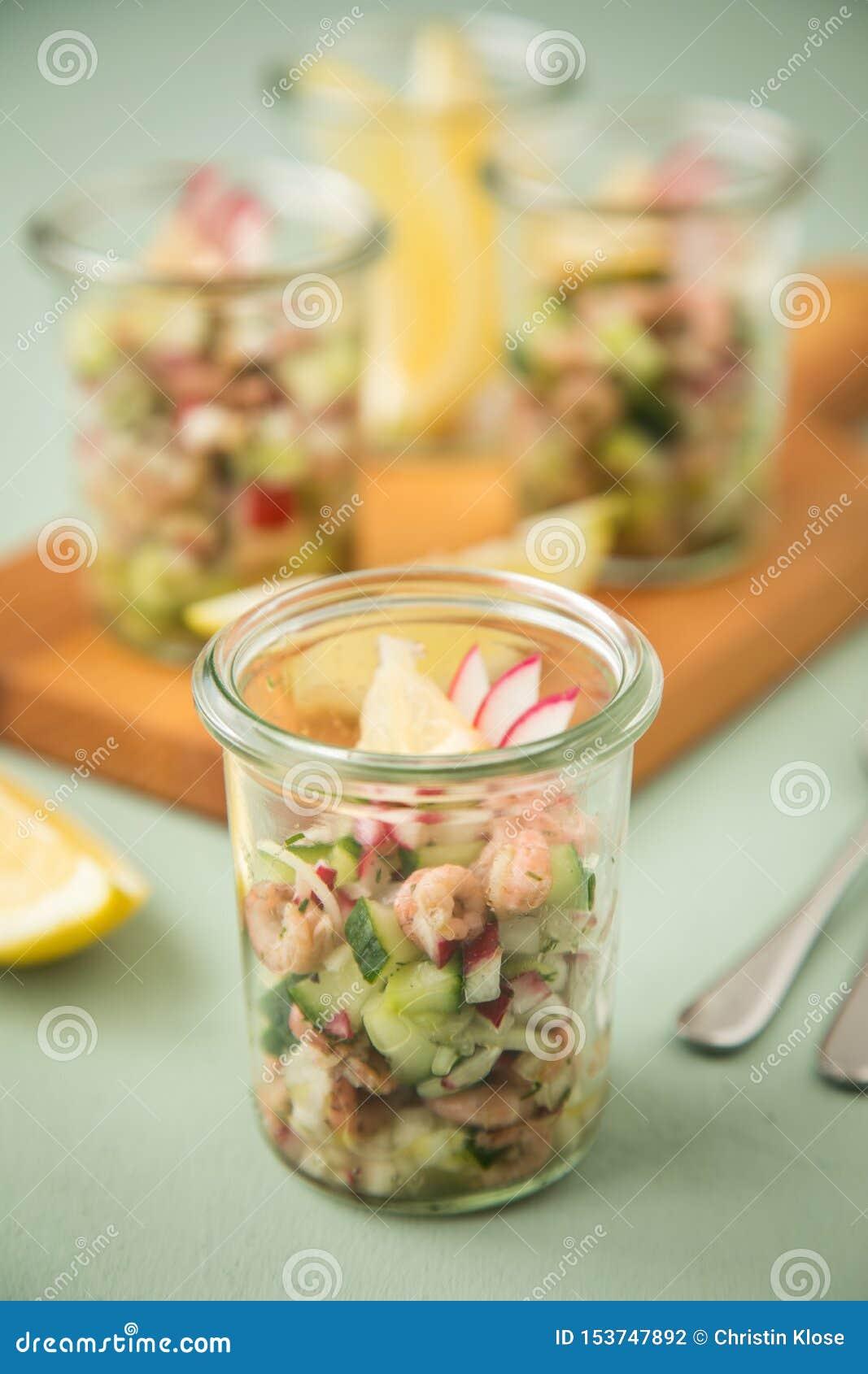 Deutscher Nordseebraungarnelensalat Frieslands im Glasbecher mit Gurke, rotem Rettich, Dill und Zitrone auf hölzernem Brett und G