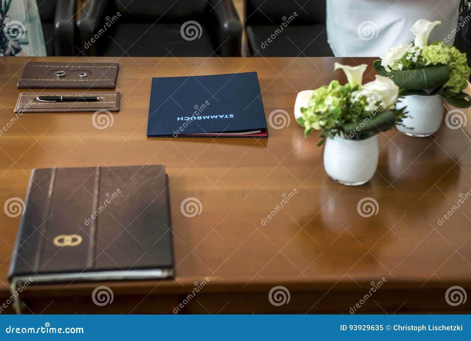 Deutsches Hochzeitshöflichehestandsregister Pen Bride Groom Rings und Blumenstrauß-frische schöne Blumen auf Holztisch