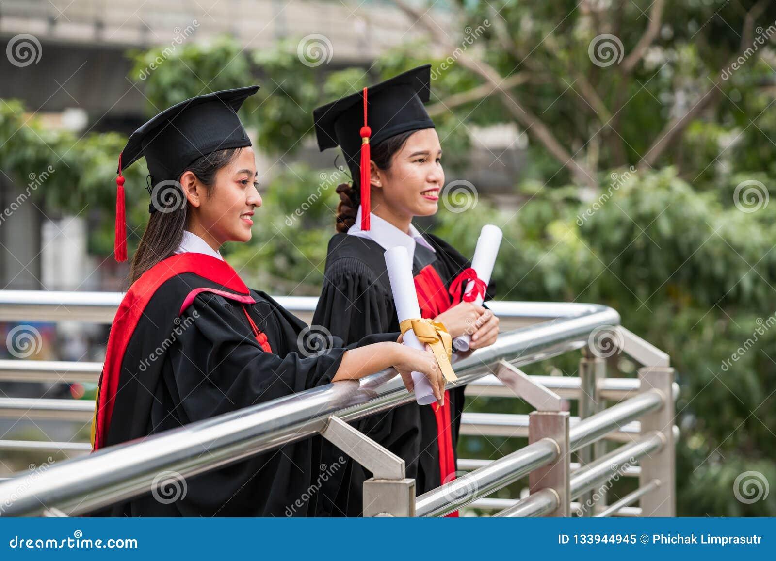 Deux étudiants asiatiques féminins de sourire dans la robe d obtention du diplôme
