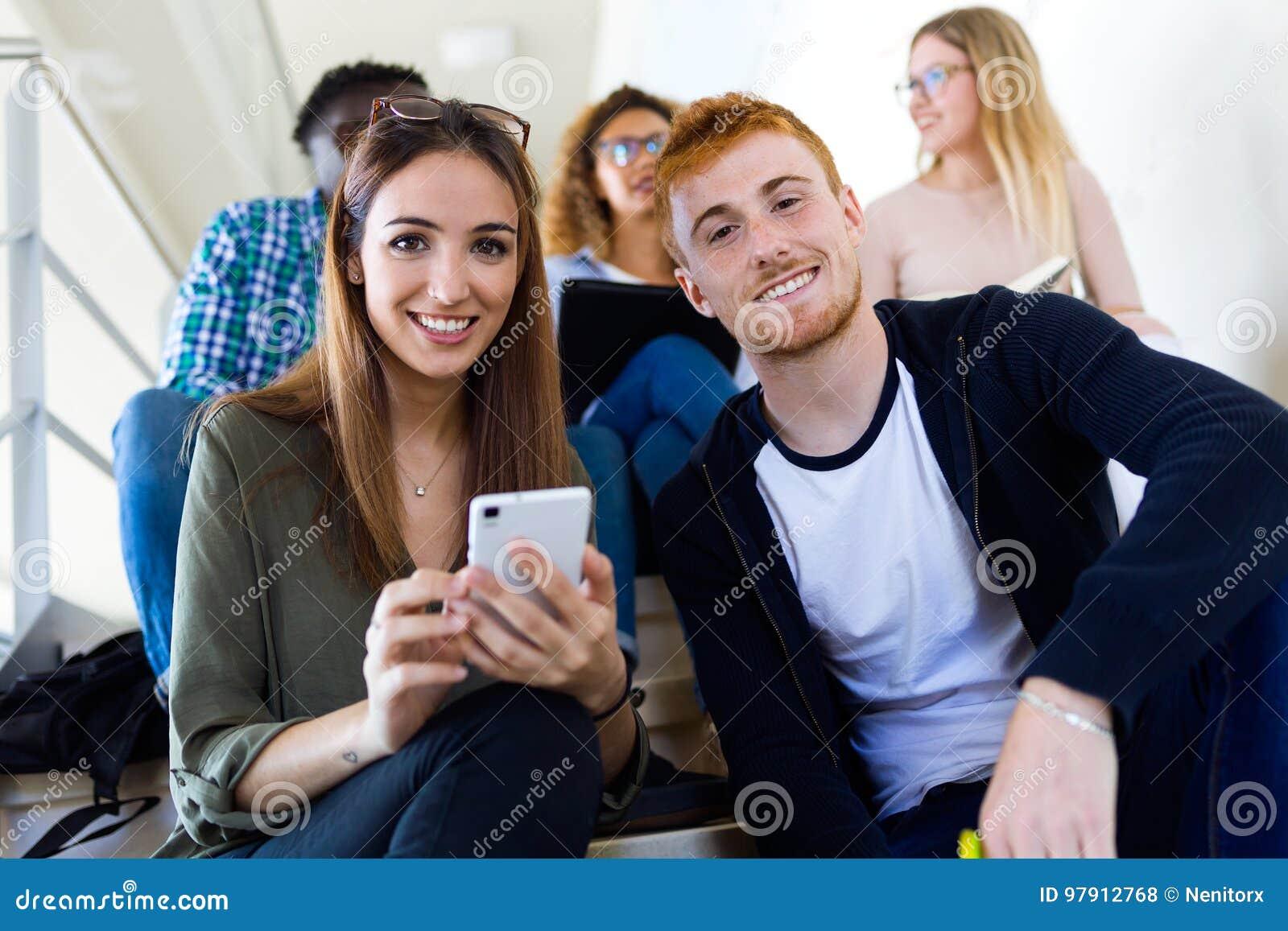 Deux étudiants employant ils téléphone portable dans une université