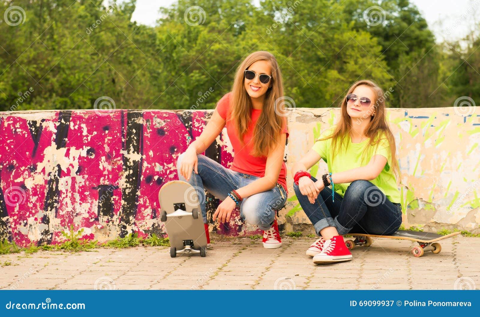 Deux amie de l adolescence ayant l amusement ainsi que le panneau de patin Outd