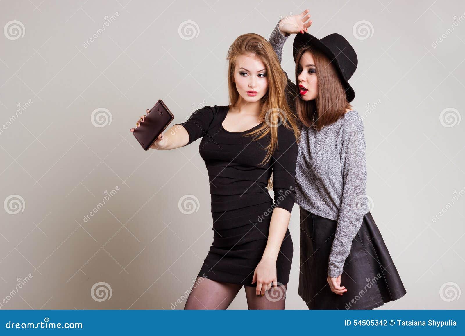 Deux amies heureuses gaies de fille ont photographié au téléphone, téléphone d individu
