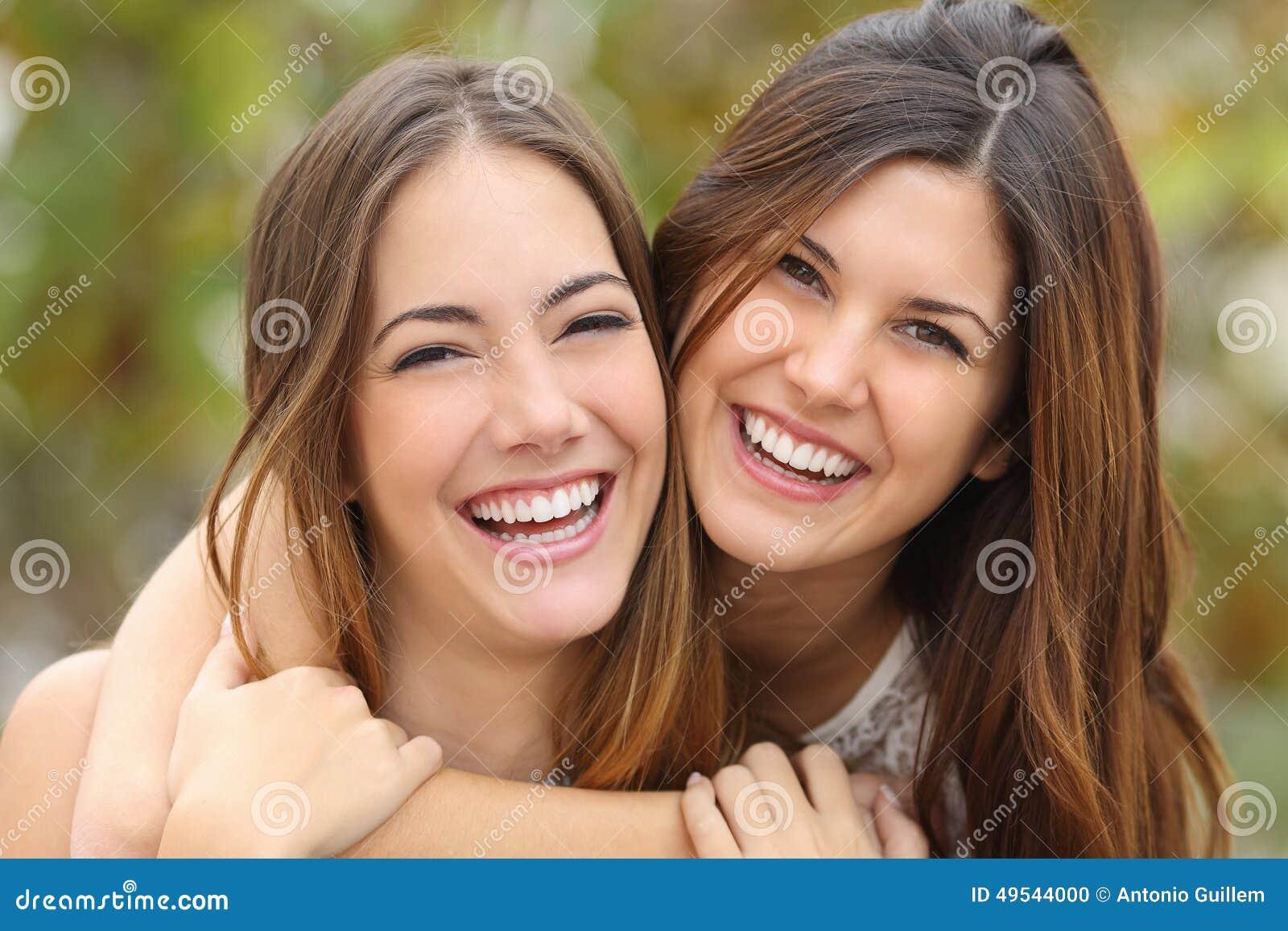 Deux amis de femmes riant avec les dents blanches parfaites