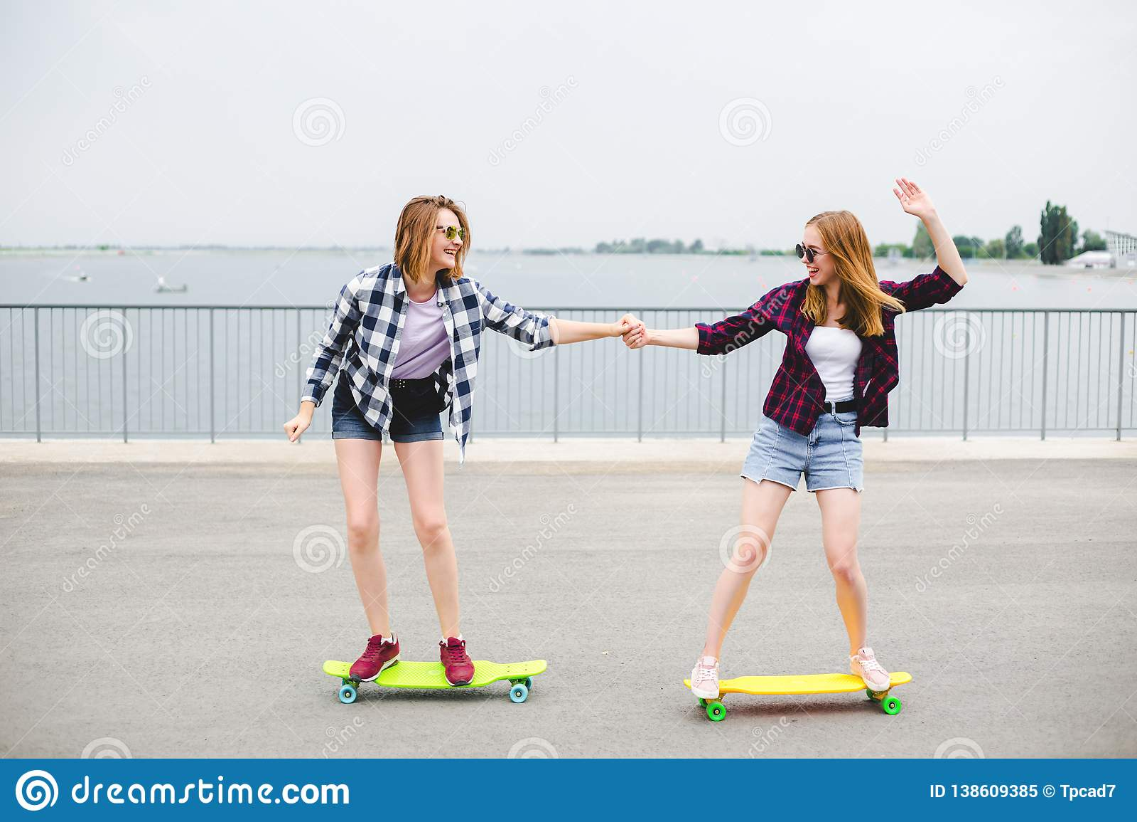 Deux amis féminins de sourire apprenant le longboard de monte avec s aider Concept d amitié