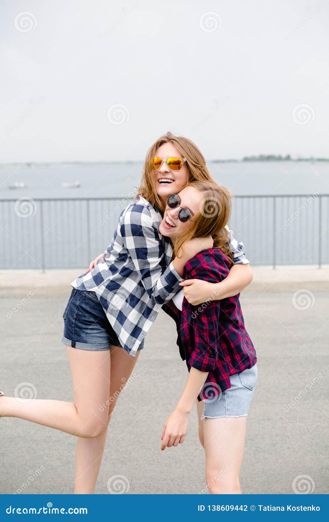 Deux amis féminins de sourire s étreignant sur la rue Concept de vacances, de vacances, d amour et d amitié