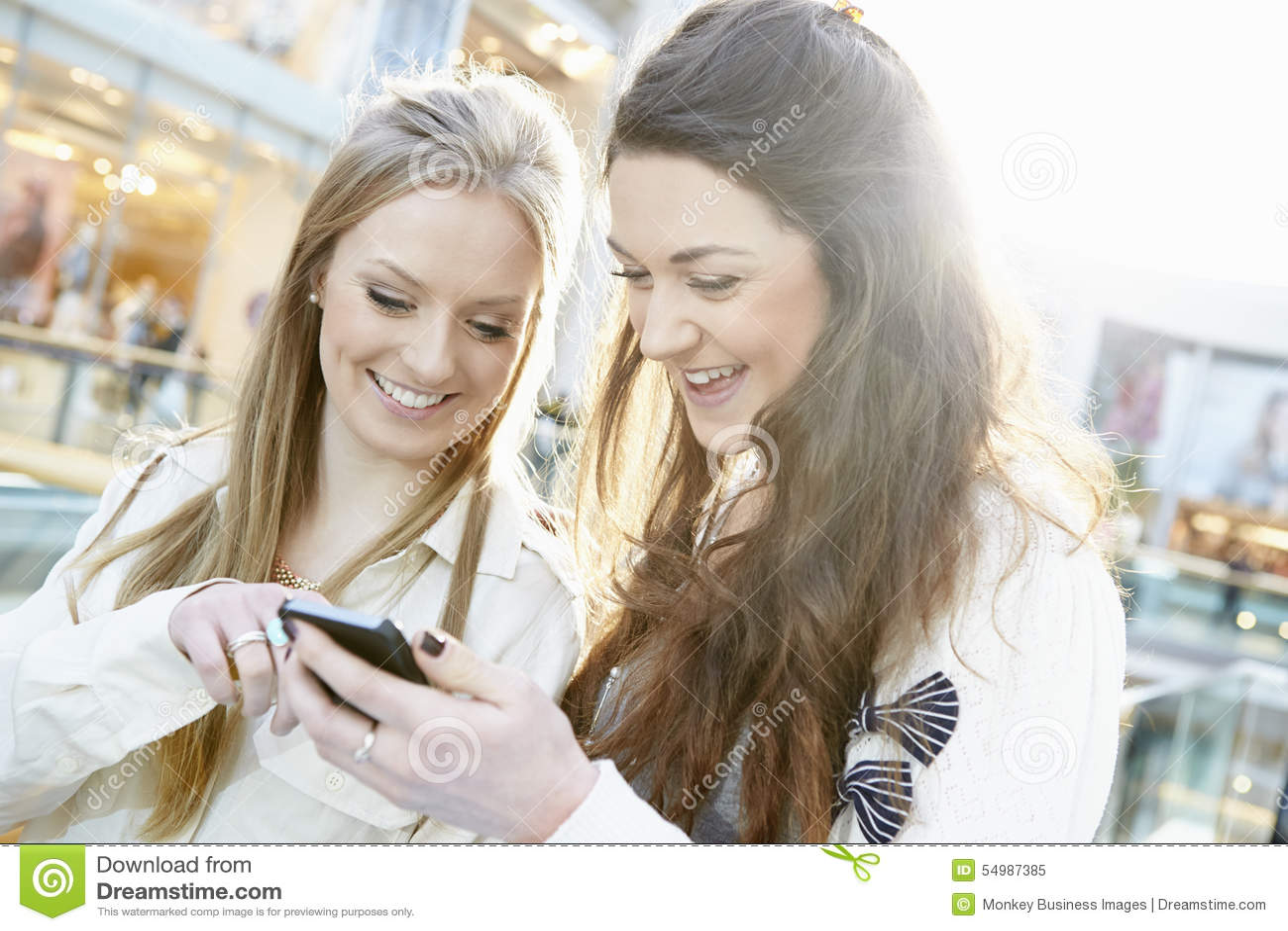 Deux amis féminins faisant des emplettes dans le mail regardant le téléphone portable