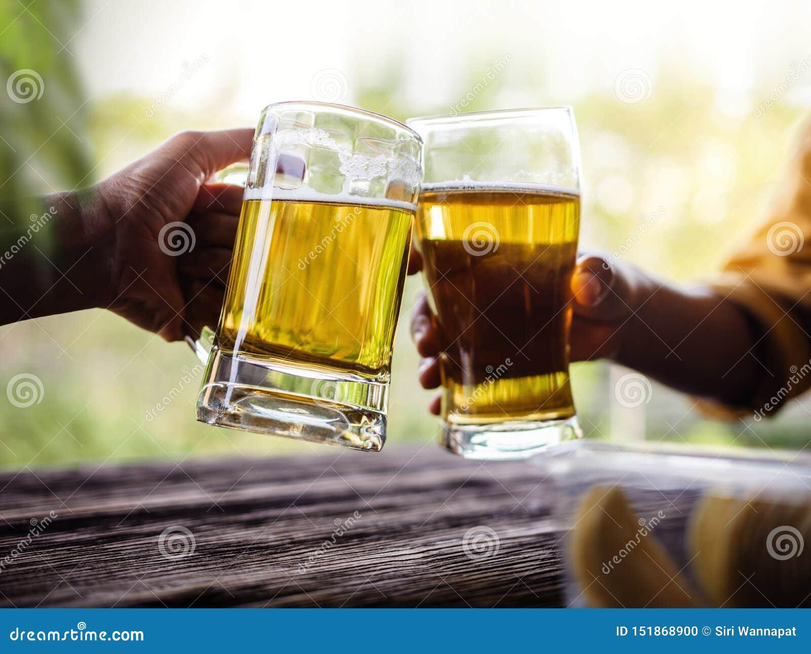 Deux amis faisant des acclamations avec des verres et buvant de la bière
