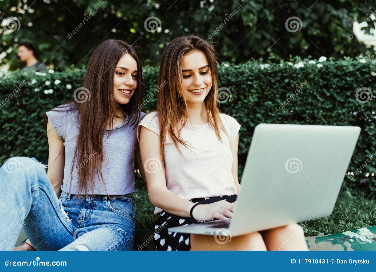 Deux amis heureux recherchant en ligne dans un ordinateur portable se reposant sur l herbe dans la rue