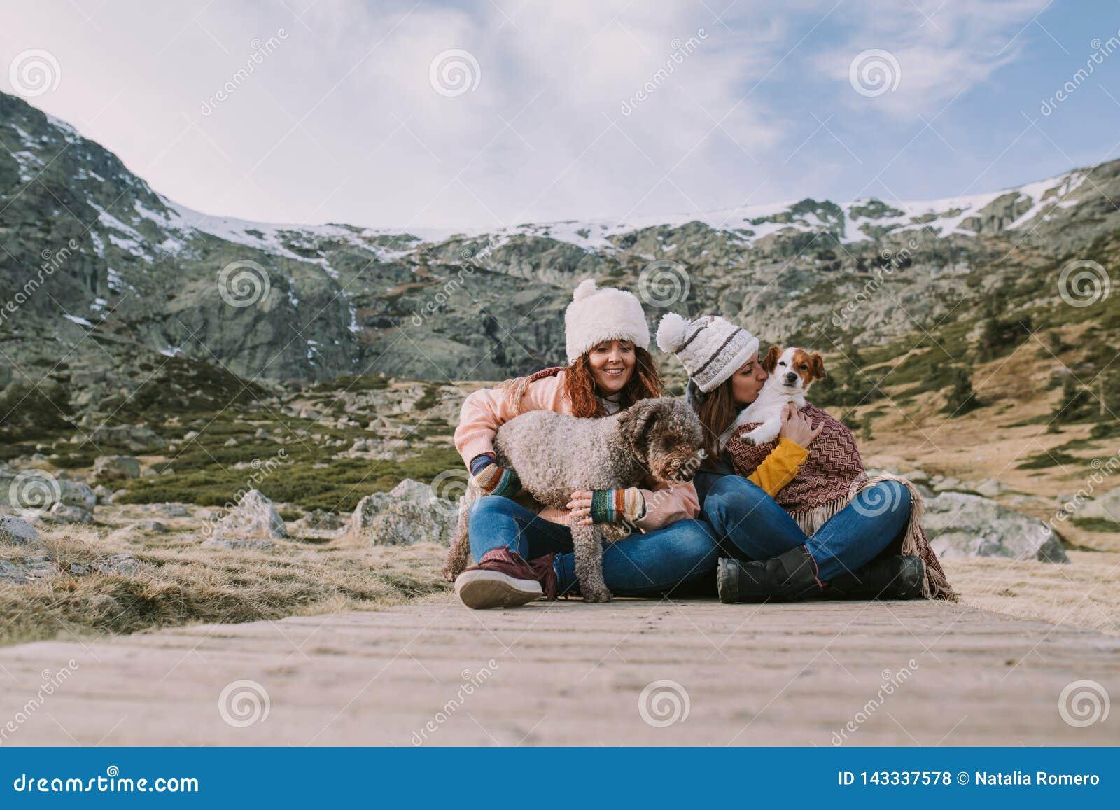 Deux amis jouent avec leurs chiens se reposant dans le pré avec une grande montagne derrière eux