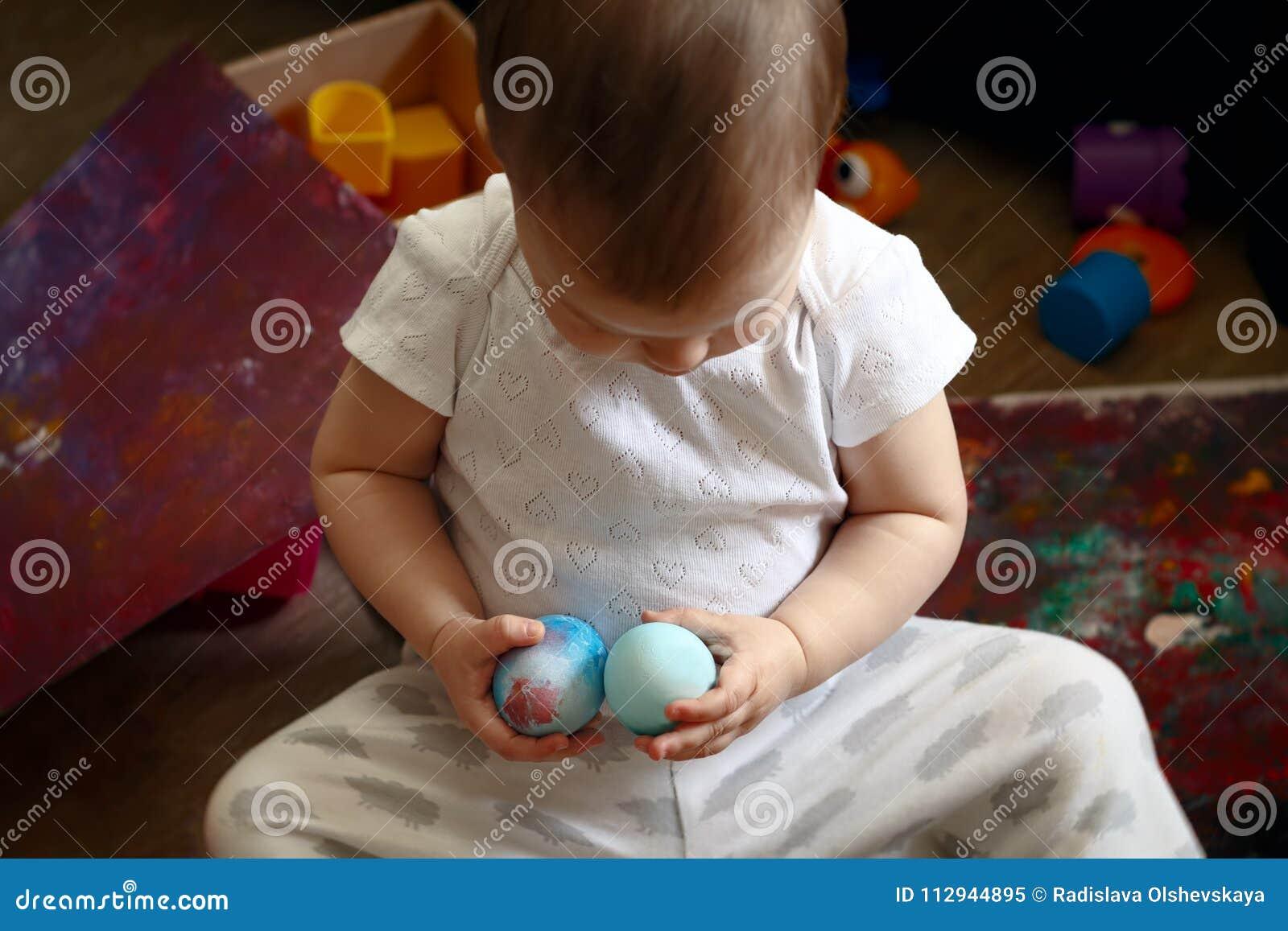 Deux années d enfant tient deux oeufs de pâques