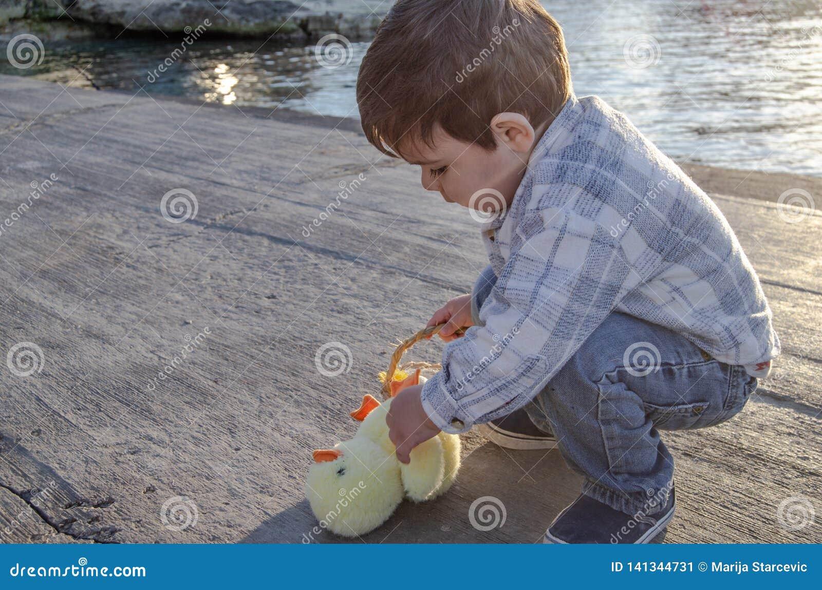Deux années mignonnes d enfant en bas âge jouant avec le petits jouet et panier de poulet avec deux oeufs de pâques sur le Doc. d