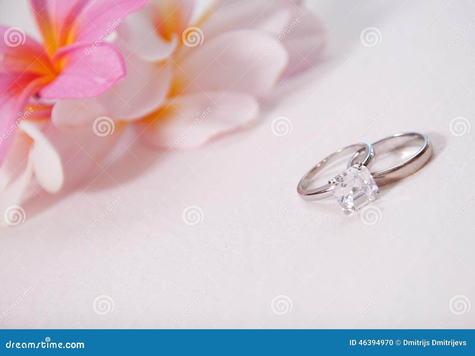 Photo de deux anneaux de mariage devant les fleurs tropicales.