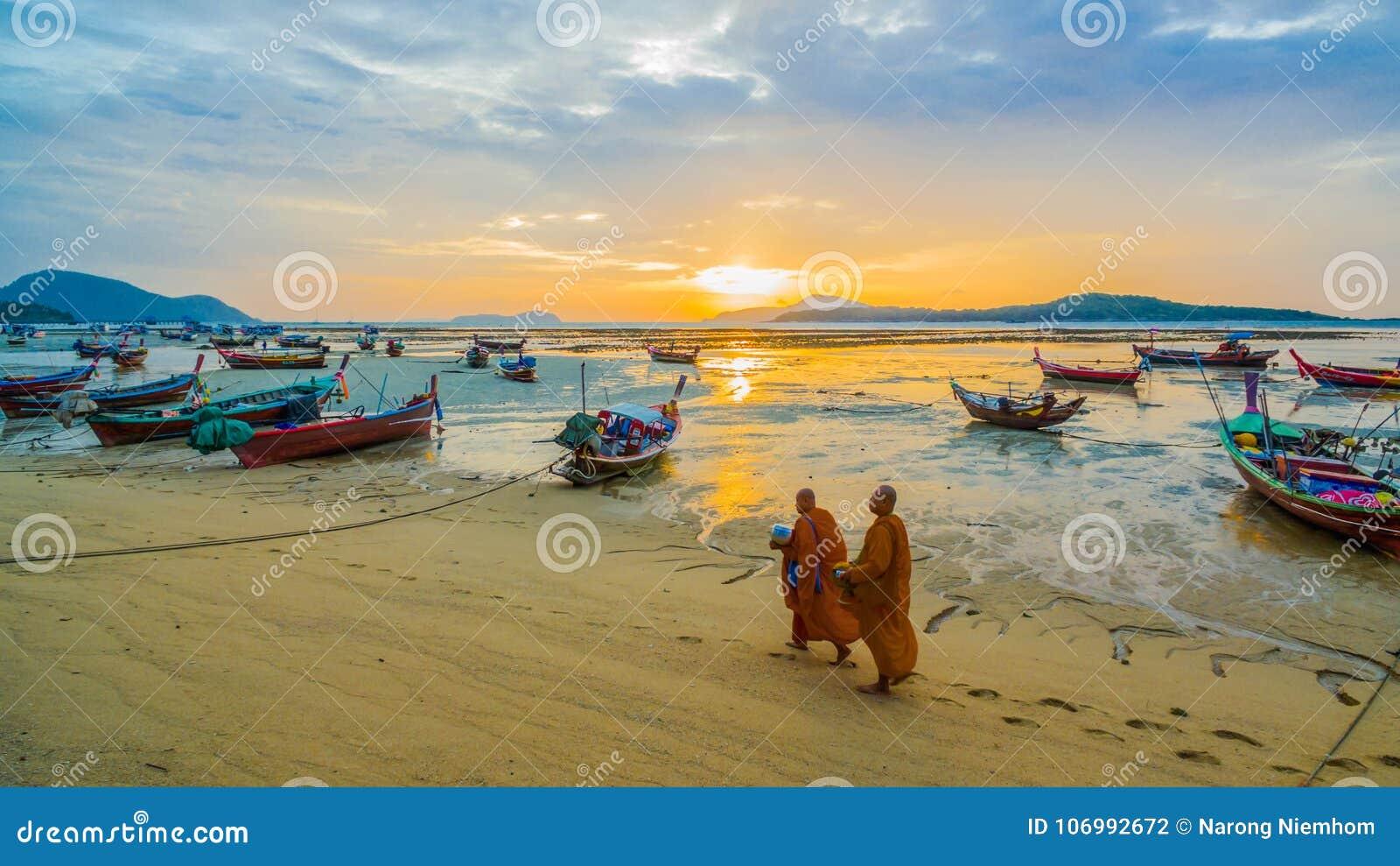 Deux aumône de marche de moines sur la plage