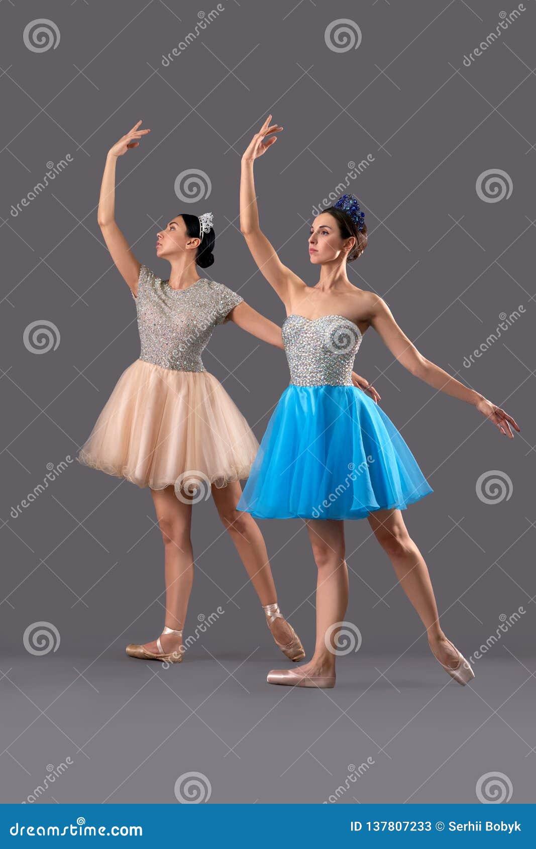 Deux ballerines dans des robes et des chaussures et pose de ballet