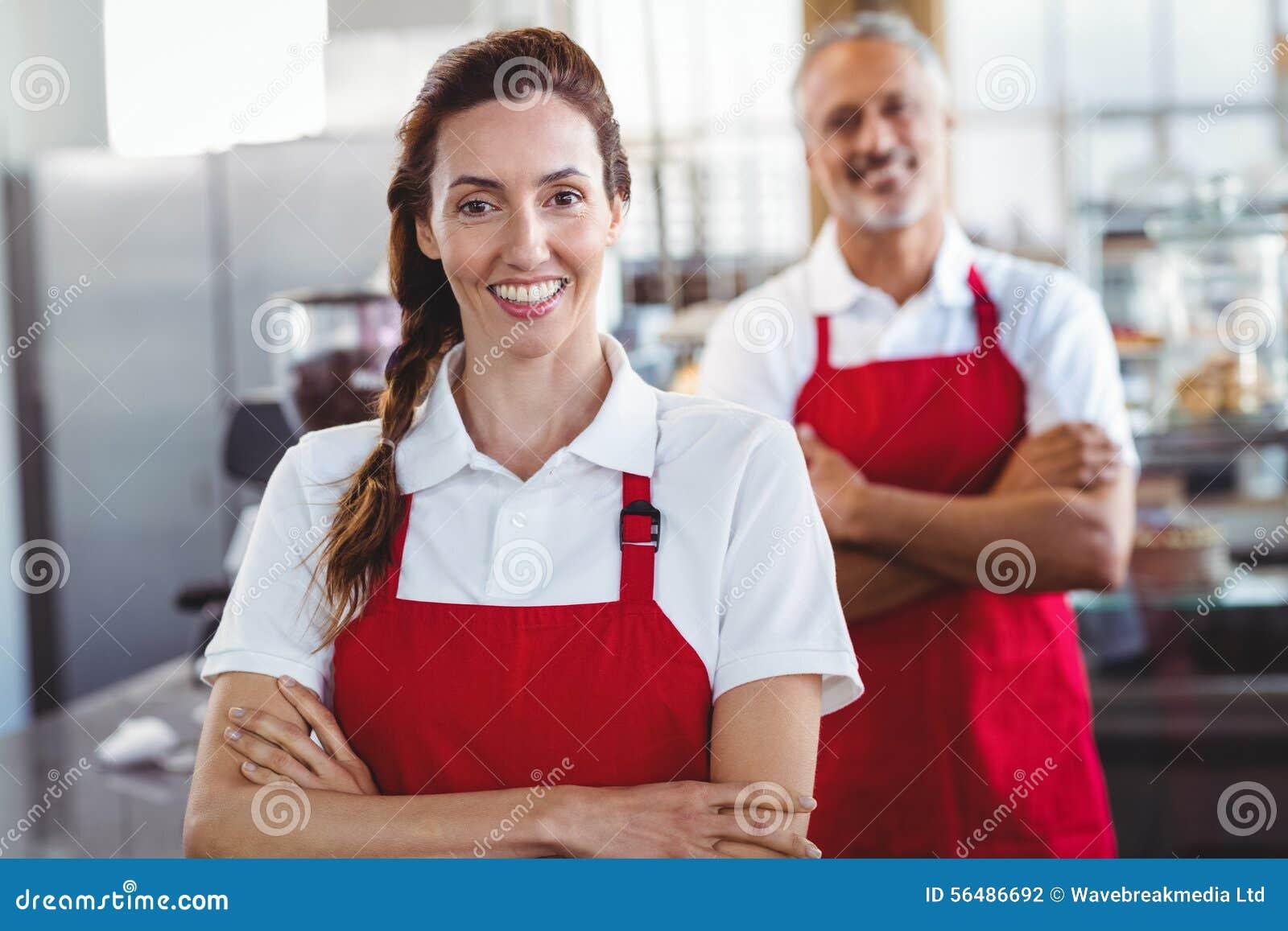 Deux barman souriant à l appareil-photo avec des bras croisés