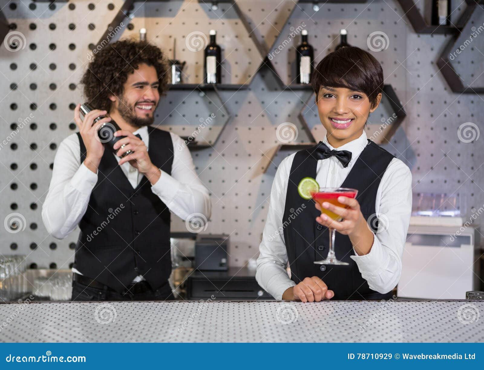 Deux barmans préparant le cocktail et servant dans le compteur de barre