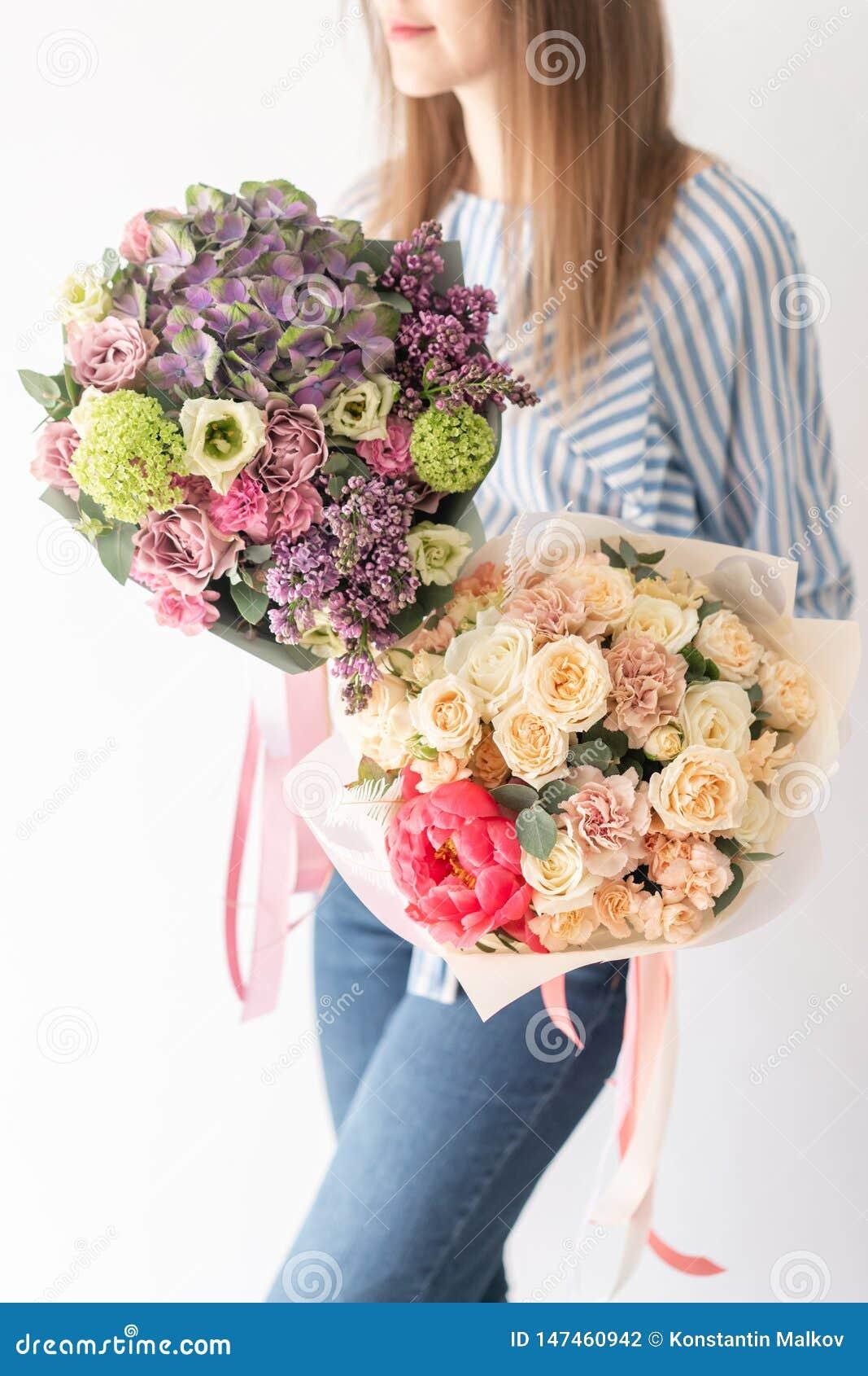 Deux beaux bouquets des fleurs m?lang?es chez les mains de la femme le travail du fleuriste ? un fleuriste Couleur en pastel sens