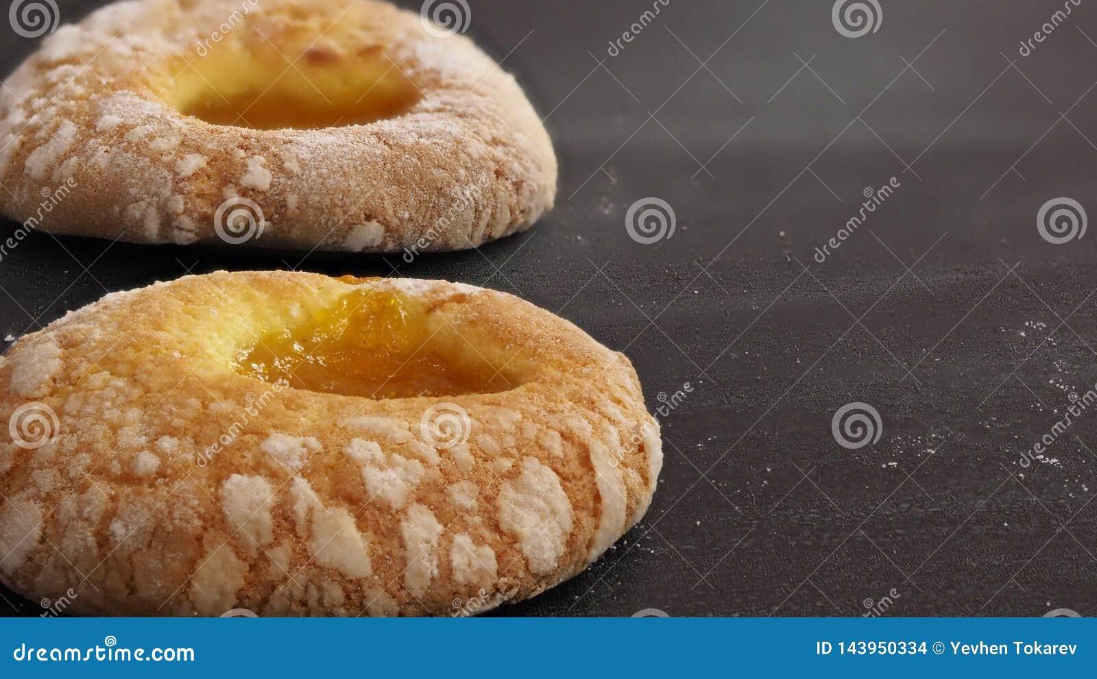 Deux beignets avec la confiture de sucre en poudre et d abricot s étendent sur la table un