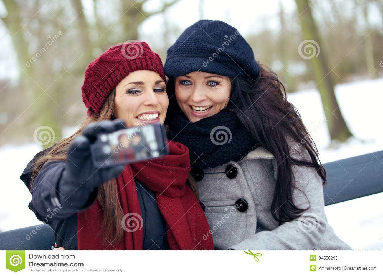 Deux belles femmes avec le téléphone d appareil-photo en parc