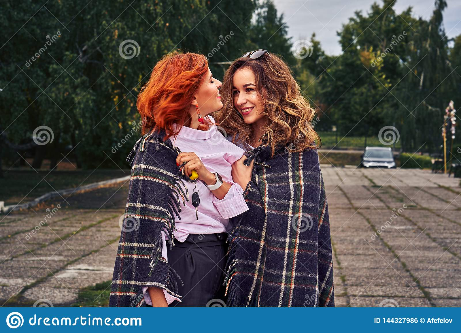 Deux belles femmes avec les cheveux rouges et bruns avec émotion communiquer