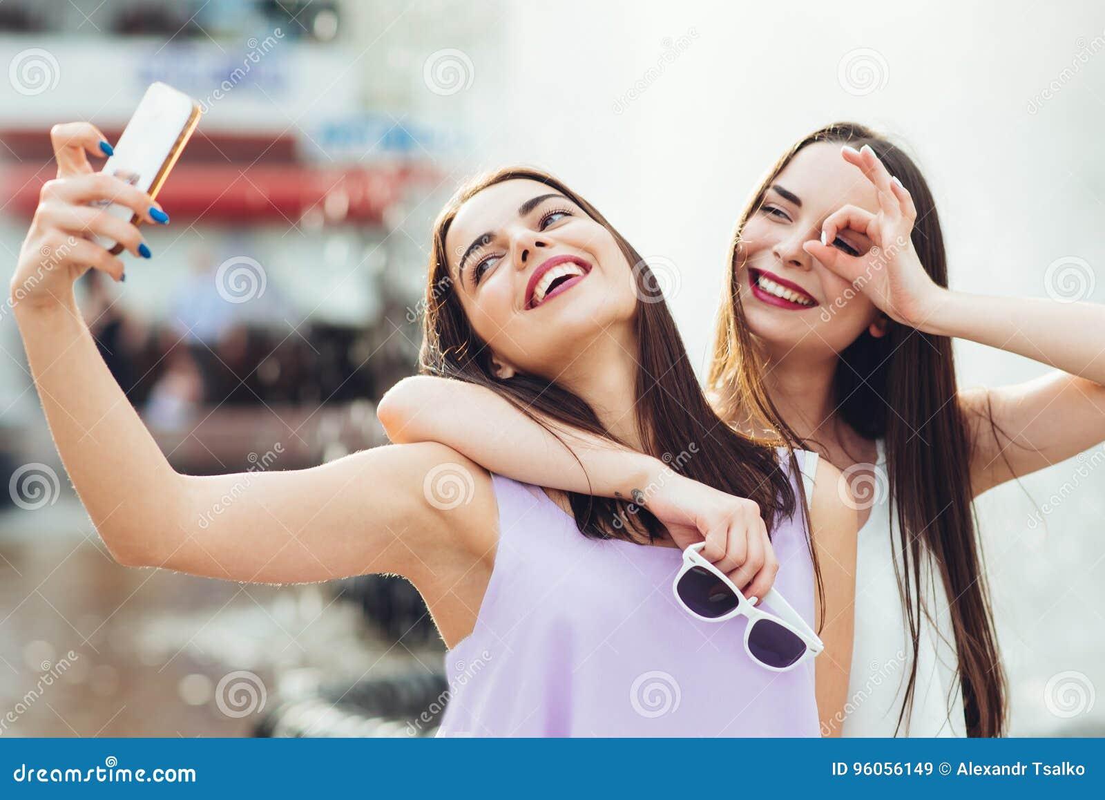 Deux belles soeurs font le selfie sur la rue