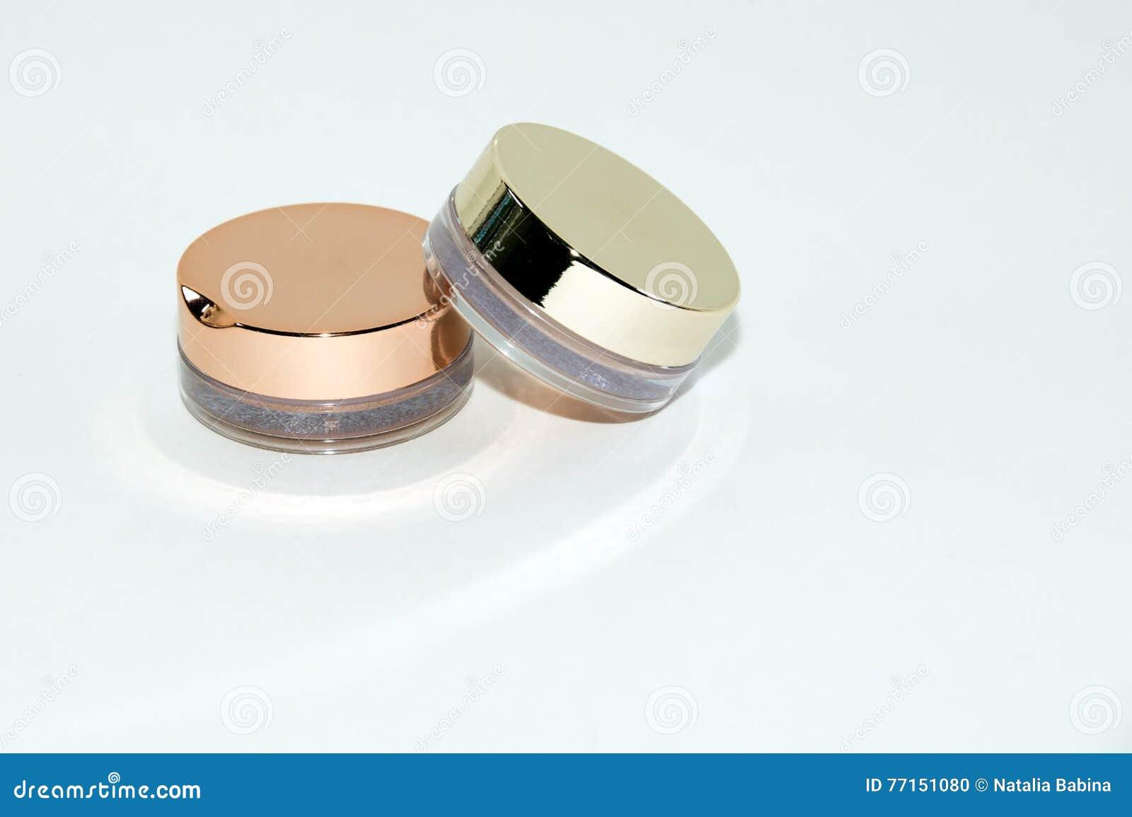 Deux boîtes en verre de fard à paupières sur le fond blanc avec les ombres molles et les réflexions