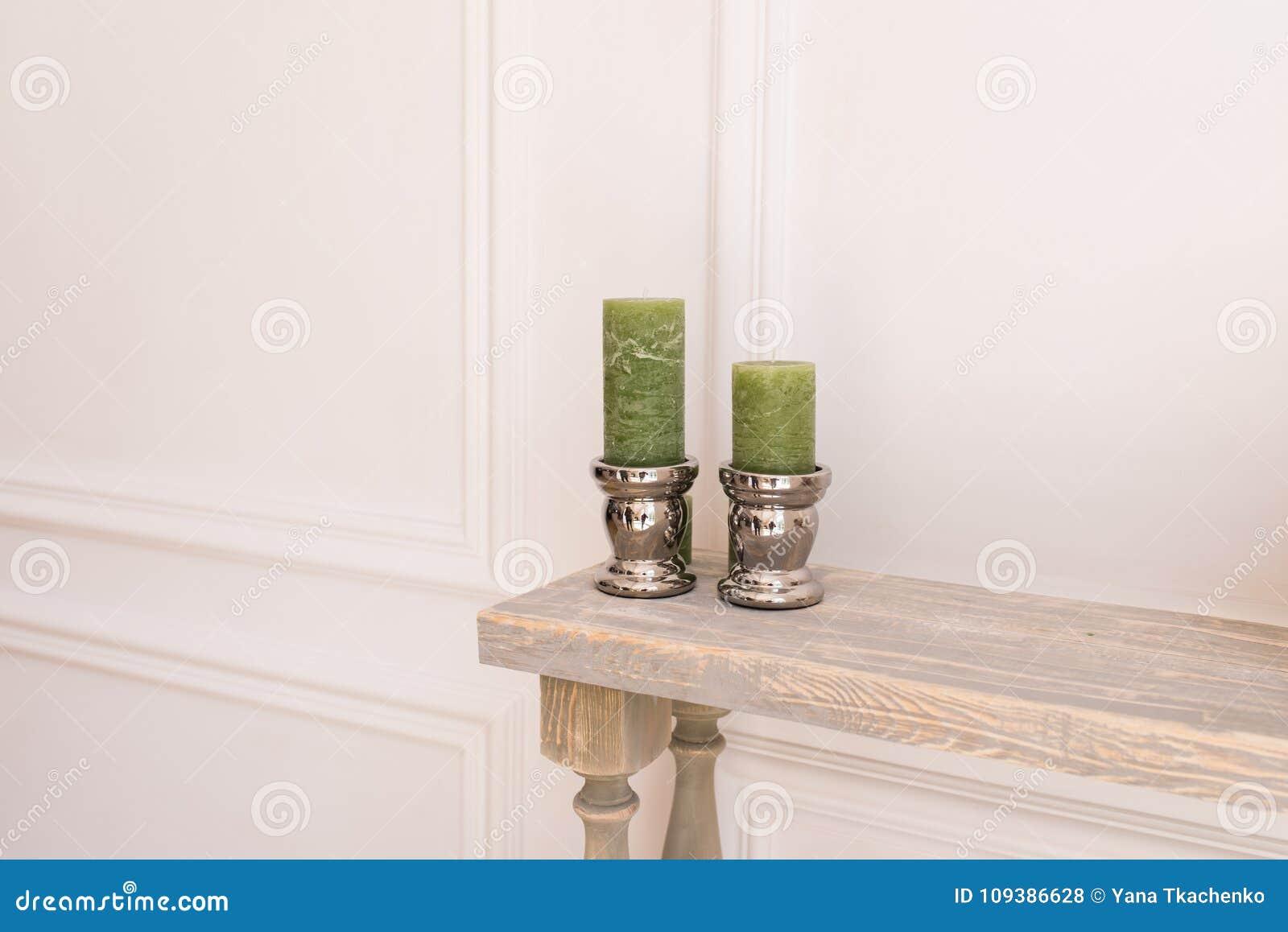 Deux bougies épaisses vertes dans un chandelier argenté